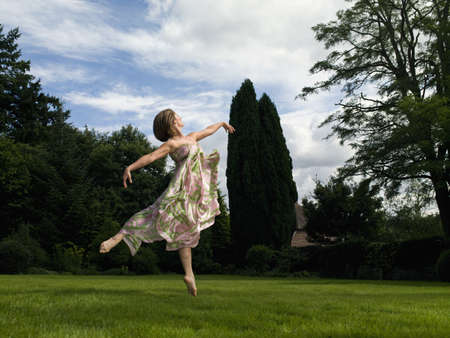 gratified: A young woman dancing in a garden LANG_EVOIMAGES