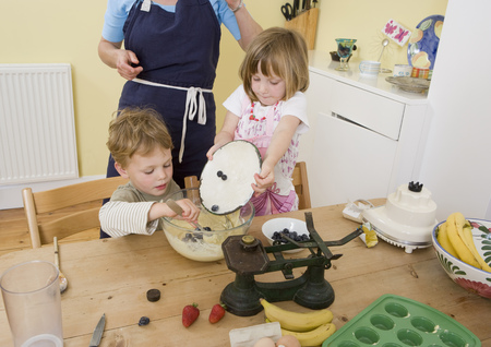 front desk: boy, girl and mum making fruit muffins LANG_EVOIMAGES
