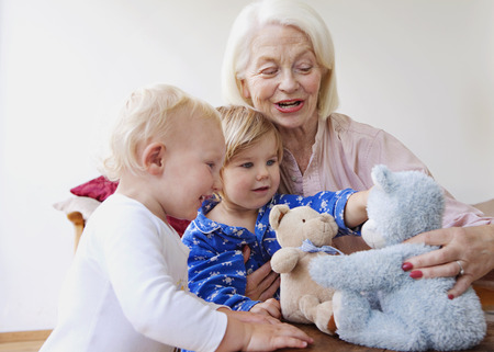 three months old: A grandmother playing with two toddlers
