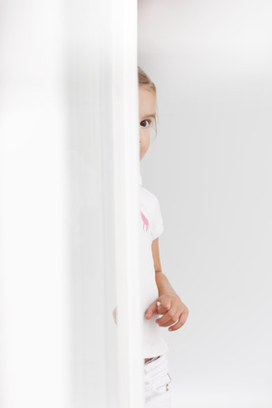 timidity: young girl looking around corner