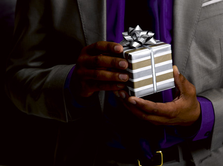 shared sharing: Business man holding gift LANG_EVOIMAGES