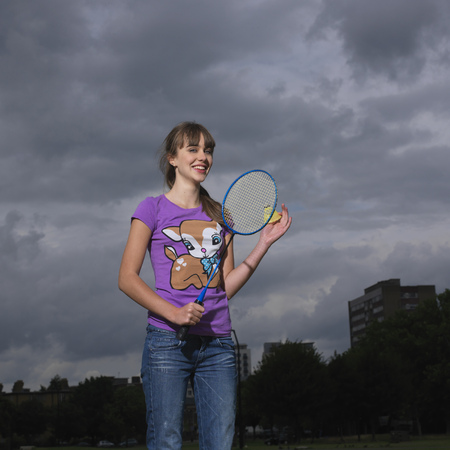 gratified: young woman with badminton racket LANG_EVOIMAGES