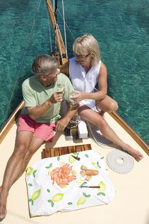 easygoing: A senior couple picnic while sailing