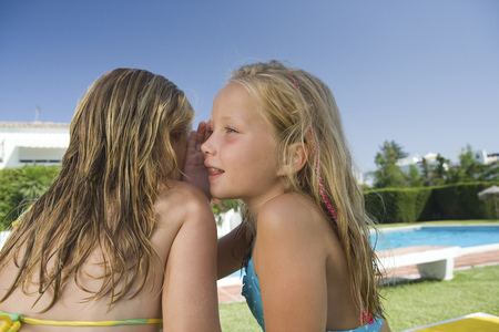 gratified: Two young girls sharing a secret by pool