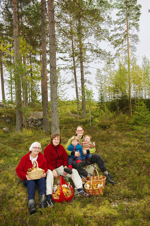 remoteness: Family with mushroom baskets in forest