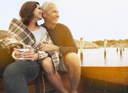Middle aged couple cuddling on old boat LANG_EVOIMAGES
