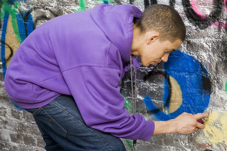 Mixed race Teenager doing graffiti