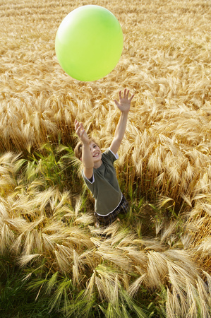 tosses: Boy playing with balloon in wheat field