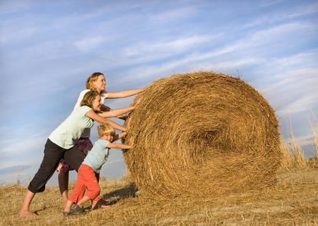 girl, woman, boy pushing hay bale