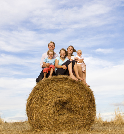 family of five sitting on hay bale LANG_EVOIMAGES