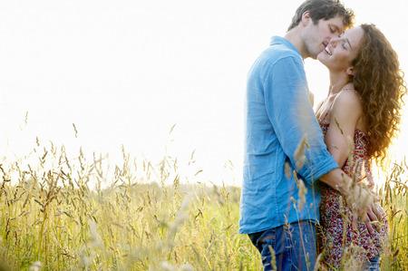 curare teneramente: Coppia baciare in un campo di grano