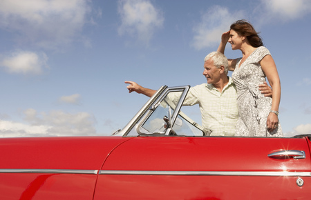 hearted: Senior couple in sports car, pointing LANG_EVOIMAGES