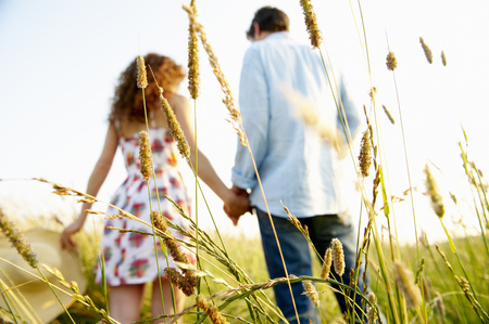 cherished: Couple holding hands in a wheat field