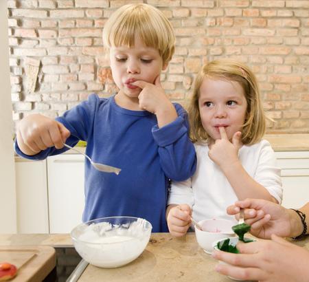 licking finger: girl, boy tasting baking ingredients LANG_EVOIMAGES