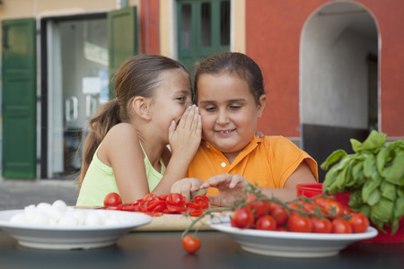 shared sharing: girls whispering whilst preparing food LANG_EVOIMAGES