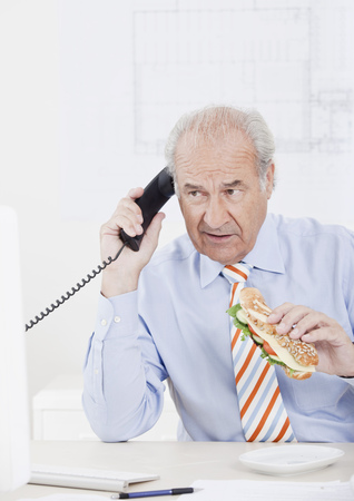 accountable: Man eating while on the phone