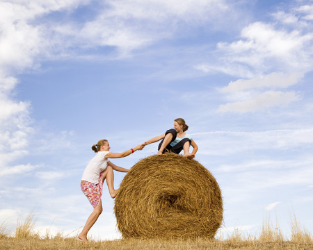 lifted hands: girl helping woman to climb hay bale