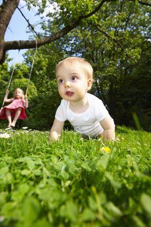 Baby in the garden, girl on the swing LANG_EVOIMAGES