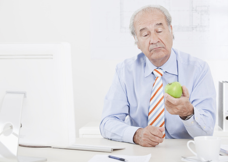 indecisive: Man looking doubtfully at an apple