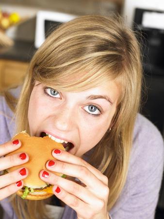 meaty: Woman eating an hamburger