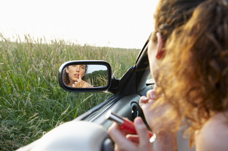 Reflection of woman in rearview mirror LANG_EVOIMAGES
