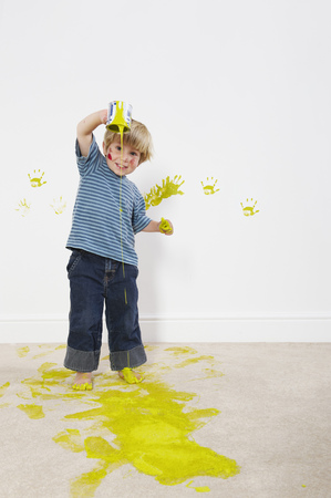 Toddler boy pouring paint onto carpet
