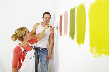 Woman painting colour swatches on wall LANG_EVOIMAGES