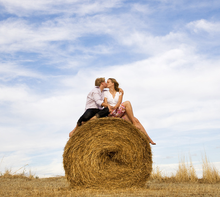 woman and man kissing on hay bale LANG_EVOIMAGES