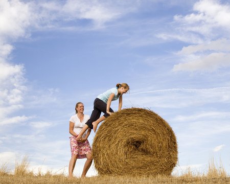 woman helping girl to climb hay bale