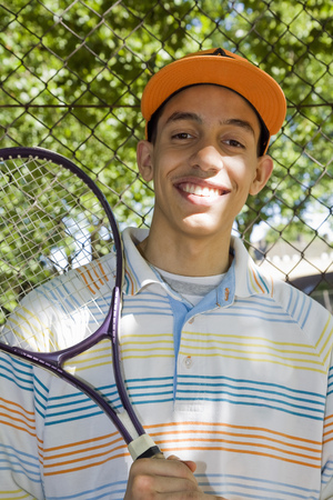 Mixed race Teenager with tennis racket