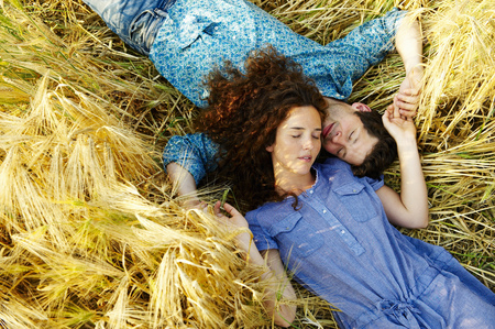 lays down: Couple laying down in a wheat field