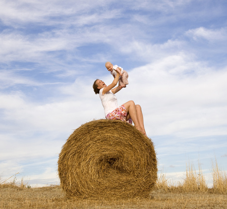 arms lifted up: woman holding baby on hay bale