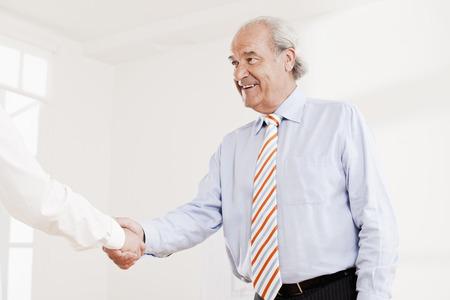70s: Senior executive shaking hands