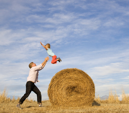man catching boy jumping from hay bale