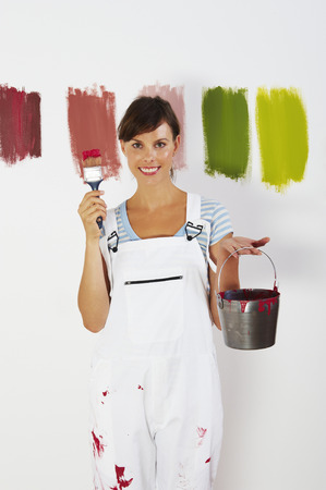Woman holding paint brush and bucket LANG_EVOIMAGES