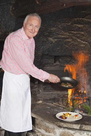 plating: elderly cook by fireplace serving food