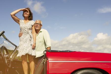 Senior couple with sports car, observing LANG_EVOIMAGES