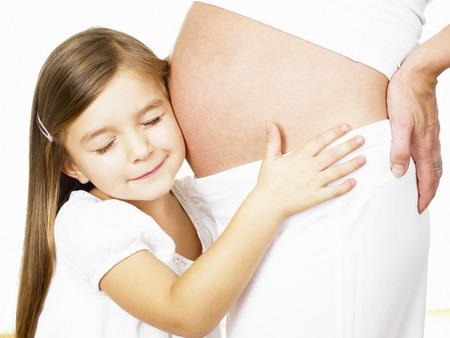 Girl hugging her mothers pregnant belly LANG_EVOIMAGES
