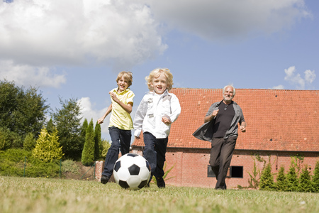 pursuing: grandfather and kids playing football