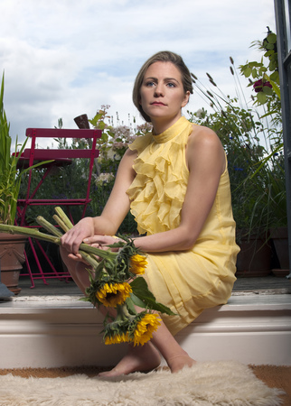 heartache: woman with sunflowers on balcony LANG_EVOIMAGES