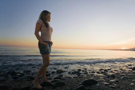 Woman on beach watching sunset low angle