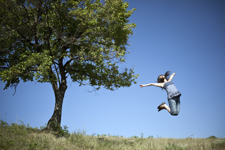 Woman jumping by tree LANG_EVOIMAGES