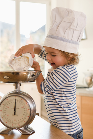 Young boy pouring flour onto scale LANG_EVOIMAGES