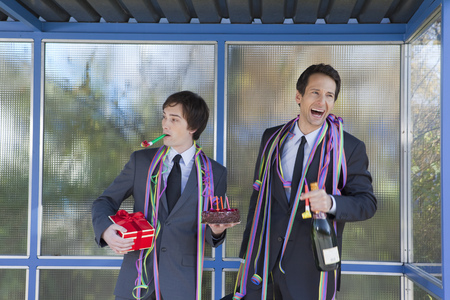 silliness: businessmen at bus stop, with party set