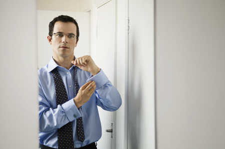 A business man doing up his cuffs LANG_EVOIMAGES