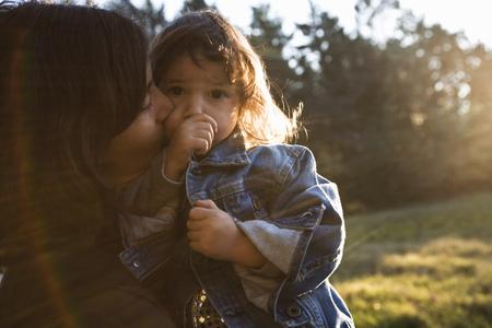 smooching: Mother hugging daughter