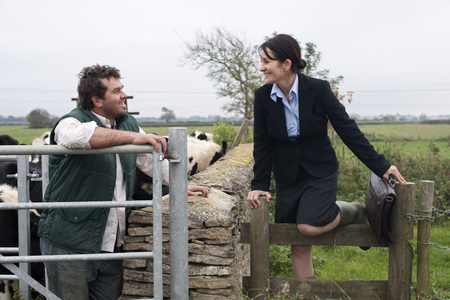 leaning by barrier: business woman talking to farmer