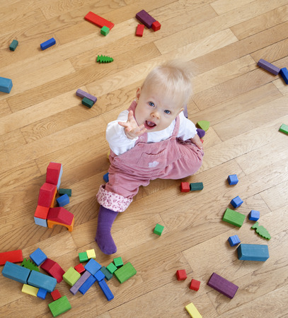 reaches: baby with toy building blocks