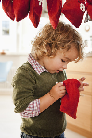 Young boy inspecting a christmas sack LANG_EVOIMAGES
