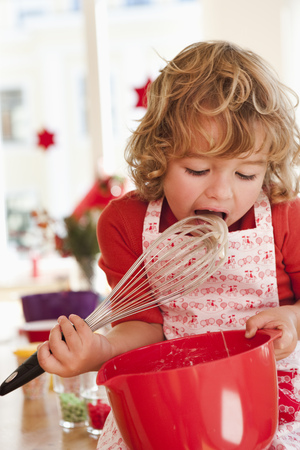 Young boy licking dough from beater